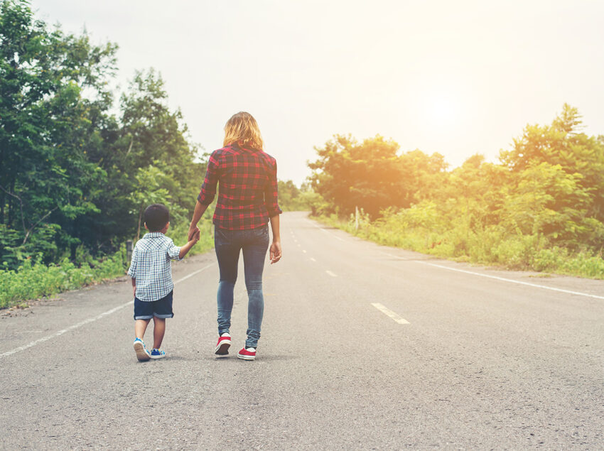 Mother holding a hand of his son in summer day walking on the st