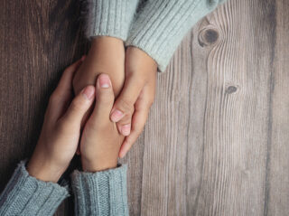 Two people holding hands together with love and warmth on wooden