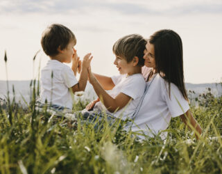 Charming young mother has fun with her little sons lying on a pl